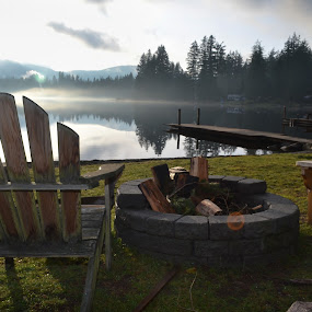 Chair and Fire Pit at Alice Lake by Adriano Sabagala - Landscapes Waterscapes ( peaceful;serene;wooden chair;fire pit;lake;alice lake; snoqualmie; wilderness; noon; fog;foggy;wooden dock; deserted;empty;logs; reflection;beauty;beautiful;overcast;cloudy;clouds;atmospheric perspective; pines evergreen cabins )