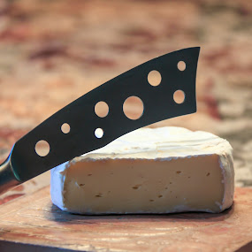 cheese knife on ceramic tile by Judith Dueck - Food & Drink Meats & Cheeses ( wine, calcium, sharp, ceramic, cheese, dairy, appetizer, board, steel, tasty, attractive, tile, eat, stainless, holes, knife )
