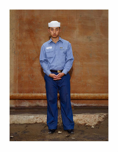 A seaman apprentice standing in front of a red wall, October 2010