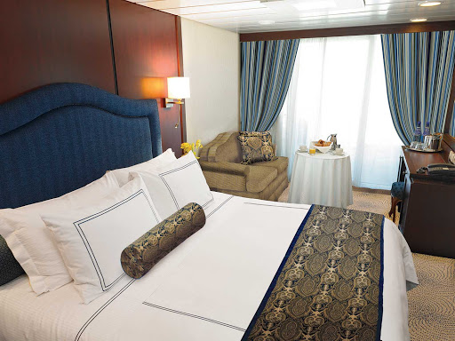Oceania-B-Veranda-Stateroom - Oceania Nautica's Veranda stateroom offers a private teak veranda for taking in panoramic views, a queen bed with 1,000-thread-count linens, a vanity desk, refrigerated mini-bar, breakfast table and spacious seating area. It's located mid-ship on deck 6 and is 216 square feet.