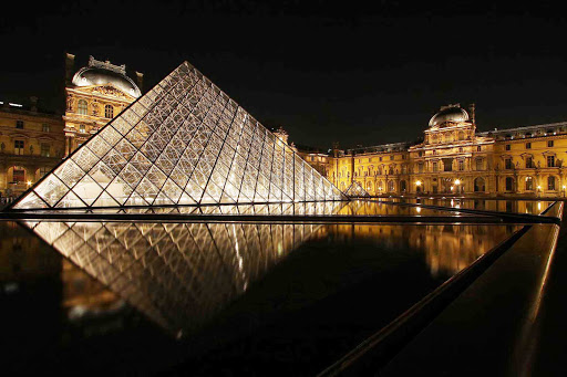 louvre-paris-france - The Louvre and its iconic pyramid at night in Paris.