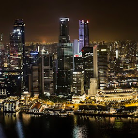 Night Singapore panorama view from Marina Bay Sans by Naďa Murmakova - Buildings & Architecture Other Exteriors ( skyline, harbor, travel, architecture, historic, attraction, city, sky, marina, light, central, structure, symbol, tourism, dusk, landmark, tourist, bay, scene, bridge, view, flyer, reflection, landscape, business, singapore, skyscraper, southeast, asia, district, evening, downtown, water, office, building, beautiful, sea, aerial, vacations, hour, urban, tower, blue, sunset, sans, night, hotel, celebration, esplanade, river,  )