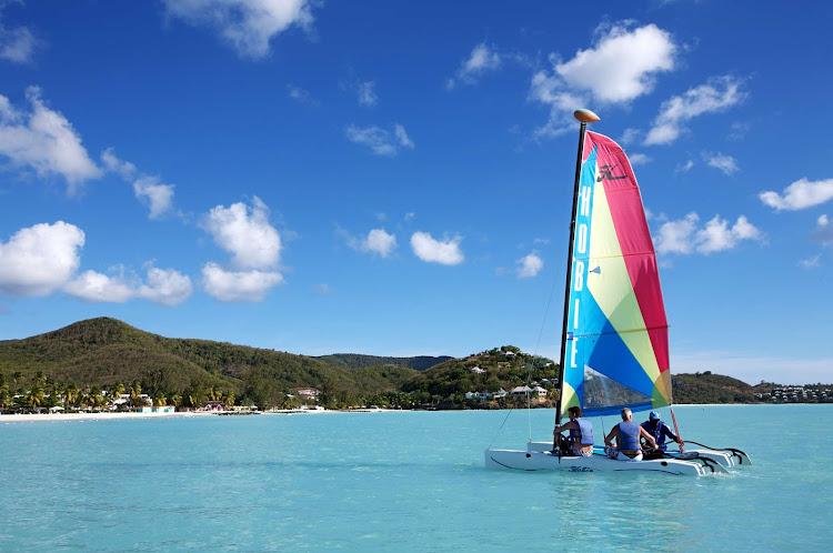 A Hobie Cat catamaran plies the waters off Jolly Beach, Antigua, in the Caribbean.