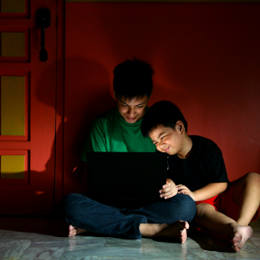 Young asian kids, brothers or siblings, with a laptop computer in a living room by Jun Pinzon - People Family ( technology, college, door, study, house, yellow, computing, kid, asian, student, family, empty, laptop, working, surf, brothers, work, orange, high school, teen, sala, youth, sitting, floor, internet, wall, mobile, computer, home, online, child, surfing, living room, den, communication, green, male, brood, web, siblings, young, studying, sit, blue, stand, pupil, brother, boy, standing )