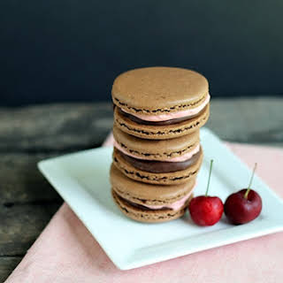 Chocolate Macarons with Cherry Frosting.