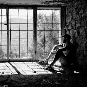 Through the window by Cassandra G - Black & White Portraits & People ( old, window, black and white, buildings, view, portrait, man, abandoned,  )
