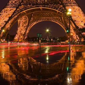 Eiffel Tower with traffic trails at dusk in the rain. by Gale Perry - Buildings & Architecture Public & Historical ( paris, eiffel tower, nighttime in the city, night life, park at night, street at night, reflections, night, close up, city at night, nightlife,  )