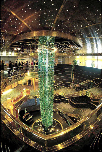 "Holland-America-Maasdam-Atrium - Holland America Line's Maasdam features Luciano Vistosi's ""Totem,"" a monumental sculpture using nearly 2,000 glimmering pieces of glass, prominently displayed in a soaring three-story atrium."