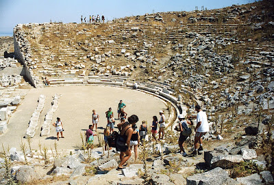A tour group from France inspects the ruins of the ancient amphitheater on the Greek island of Delos.