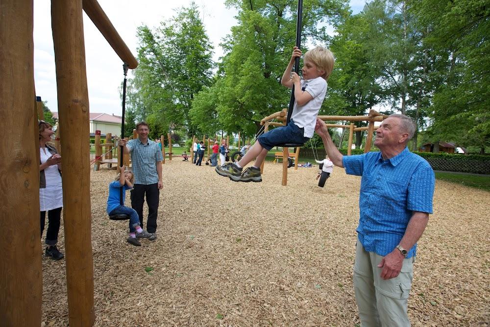 Du siehst einen Opa, der seinem Enkelkind beim Klettern hilft.