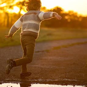 young boy running by Keren Woodgyer - Babies & Children Children Candids ( playing, photograph, jumping, happy, sunset, outdoors, age 7, fun, running, golden, outside )