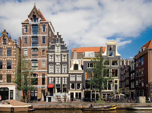 Amsterdam-facades-houses-Holland - Traditional buildings on a canal in Amsterdam, capital of the Netherlands.