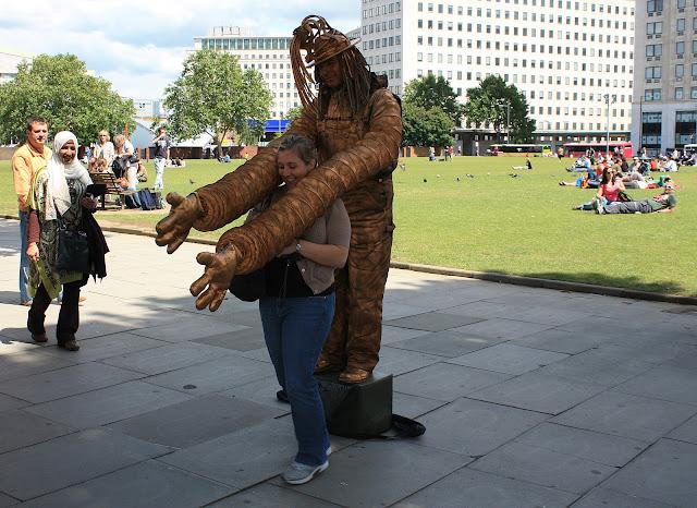 Zábava v podání pouličních umělců na břehu Temže u London Eye.