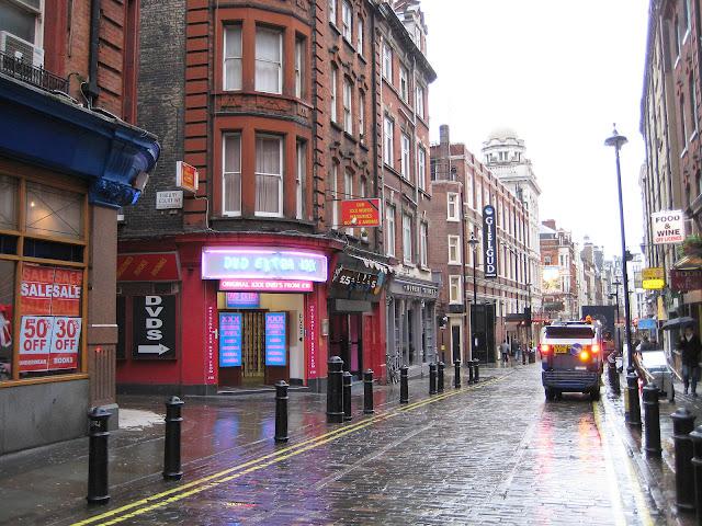 Ulice v SOHU s nepřeberným množstvím obchodů pro dospělé v typickém londýnském počasí.