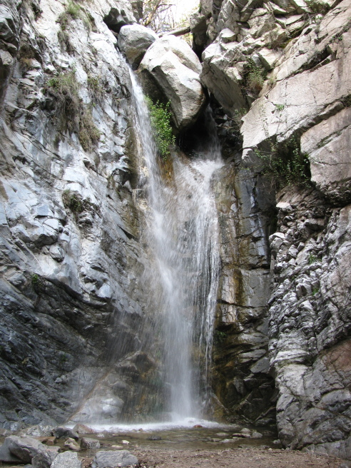 The waterfall, a couple huge boulders lodged in the top causing the water to flow into two somewhat equal streams that pour across each other.