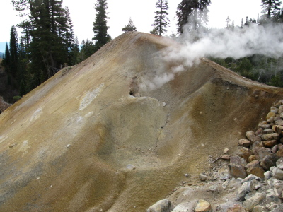 A smoking hole in a yellow mound.