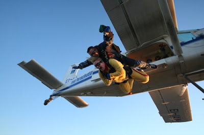 image shows two people jumpsing out of a plane, the guy behind delighted, the guy in front of him, dressed in yellow, scared out of his tree, like I'll be doing