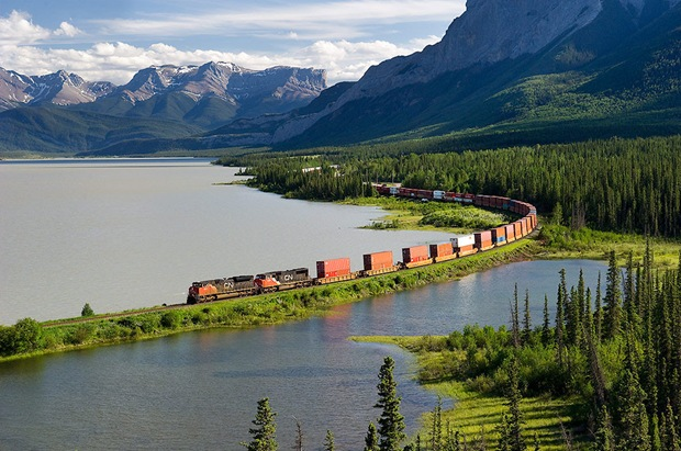 Train swings through a curve along Brule Lake with the Miette and Brule ranges providing the back drop.