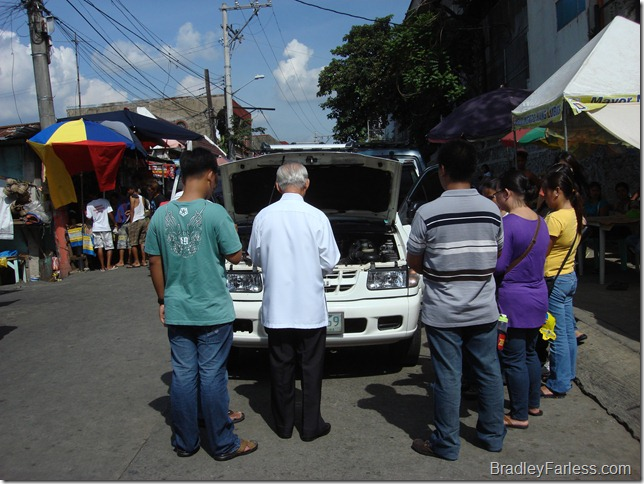 A car being blessed by a Catholic priest in the Philippines.