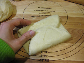 a process photo showing how the other end is folded to meet the other end of the dough in the middle of the oval