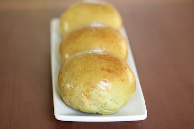 three matcha bread rolls on a white plate