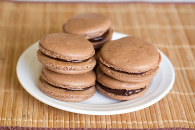 photo of chocolate macarons piled on a plate