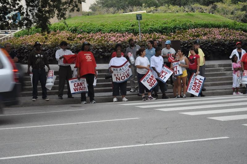 bus riders wait to cross street