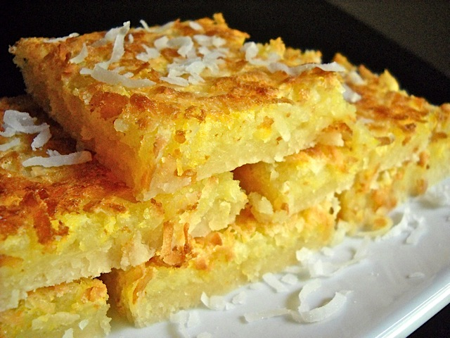 Lemon Coconut Bars cut into squares and plated on white plate