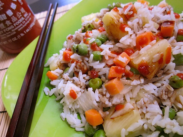 Coconut Rice Pilaf on green plate with chop sticks and bottle of sriracha on the side