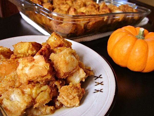 Pumpkin Bread Pudding on white plate with pan of bread pudding in background and staged with mini pumpkin
