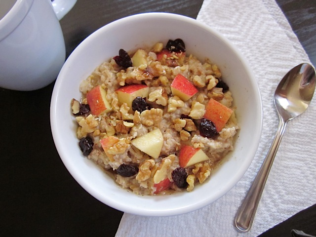 top view of autumn winter fruit and nut oatmeal in white bowl with paper towel and spoon on the side
