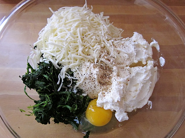 """spinach lasagna filling in clear mixing bowl ( """"dry"""" spinach, egg, ricotta, mozzarella, parmesan, salt and pepper)"""