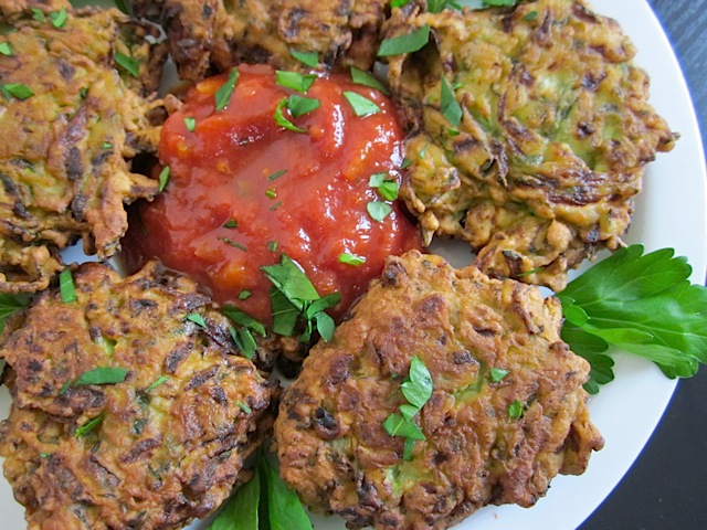 Zucchini Fritters plated on white plate with dipping sauce in the middle