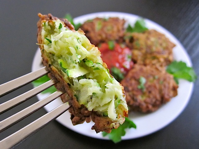 close up of zucchini fritter bite on fork with plates of fritters in background