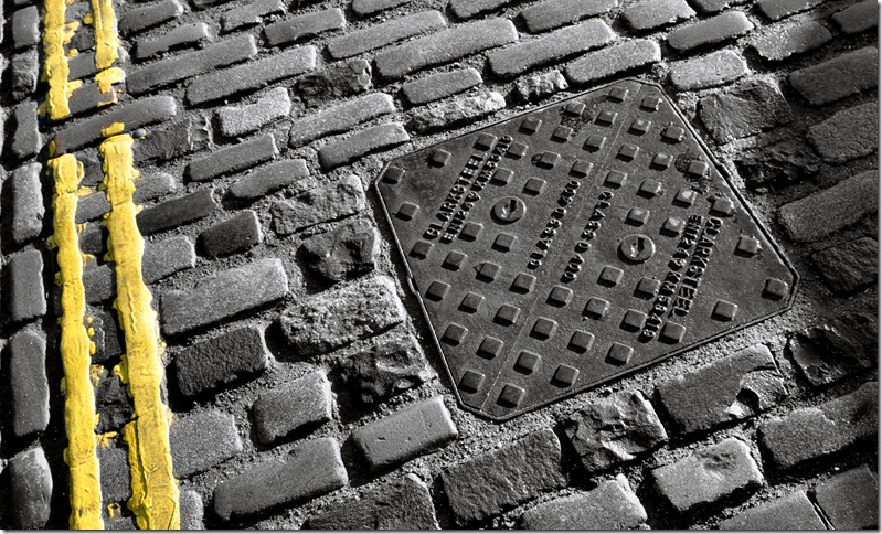 cobbled street with drain cover and painted double  yellow lines