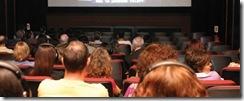 Pessoas vistas de costas em uma platéia. A imagem mostra parte de uma tela de cinema