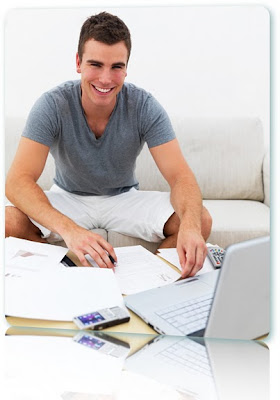 A smiling man with a laptop and a ton of paperwork.
