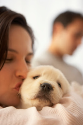 Woman kissing a dog with a man in the background.
