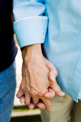 Holding an elderly person's hand.