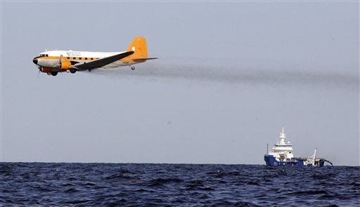 In this Tuesday, April 27, 2010 file photo, a dispersant plane passes over an oil skimmer as it cleans oil in the Gulf of Mexico near the coast of Louisiana. A preliminary test suggests that oil dispersant is washing up on Alabama beaches. AP Photo / Patrick Semansky
