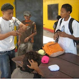 Marvin the sports instructor teaching bracelet making to a boy just back from school