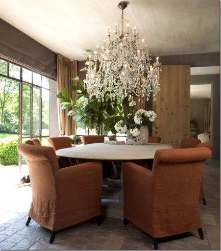 The Dining Table Is Surrounded By A Mass Of Arm Chairs, Slipped In  Persimmon Linen. The Iron Framed Windows Open To The Terrace, But Can Be  Covered Against ...