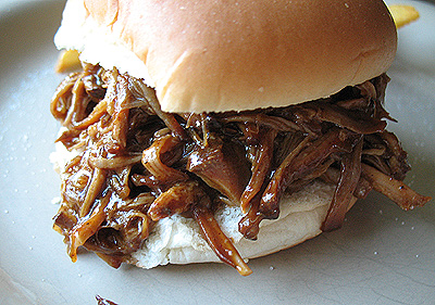A close up photo of a slow cooker pulled pork sandwich.