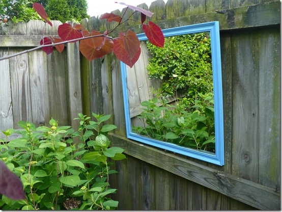 blue mirror in the garden hanging on the fence behind hydrangeas