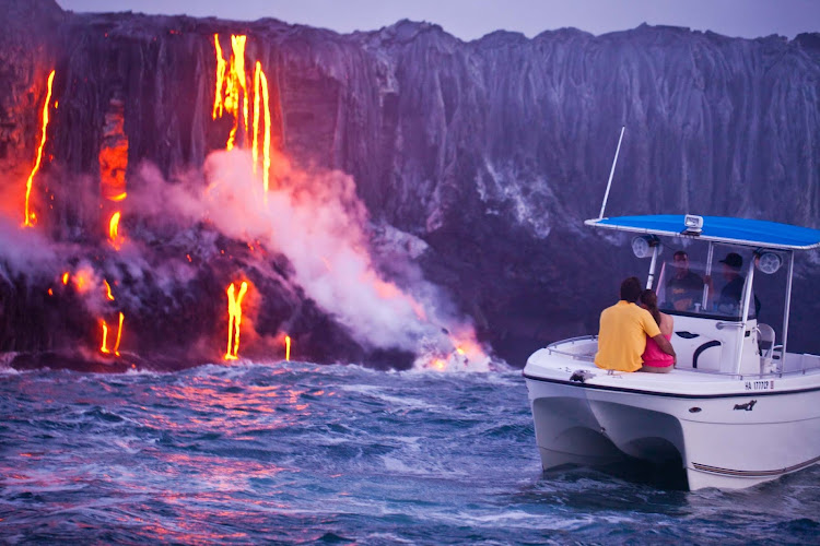 A couple watches a volcano's magma stream into the ocean on the Big Island of Hawaii.