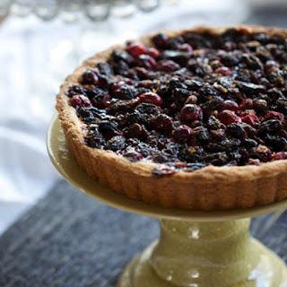 Cranberry Tart with Cognac-soaked Raisins, Tangerine Zest, and Dark Chocolate.