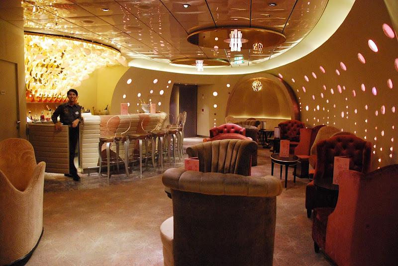 A waiter staffs an entertainment lounge bar aboard Disney Dream.