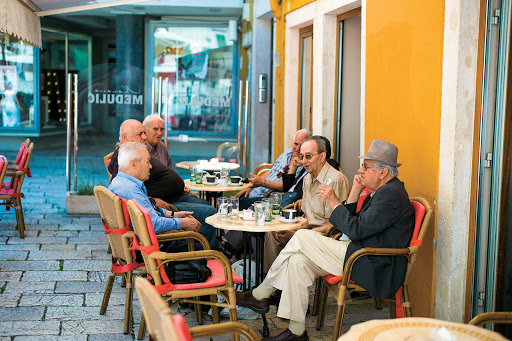 Local residents converse over coffee and drinks at a café in Croatia, one of the stops along a Mediterranean itinerary aboard Tere Moana.