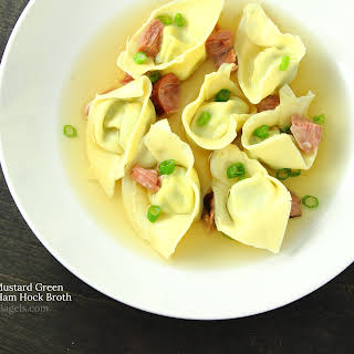 CHEDDAR AND MUSTARD GREEN TORTELLONI WITH HAM HOCK BROTH.