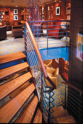 Celebrity_Millennium_Words_Library - Words, Celebrity Millennium's two-story library, features a spiral staircase, glass walls and deep armchairs. It's the ideal place to snuggle up with a good read.